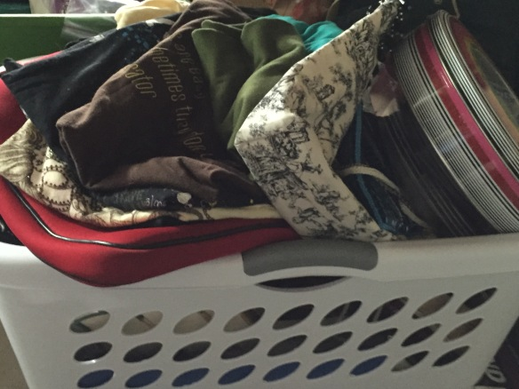 A laundry basket filled with items to sell/donate